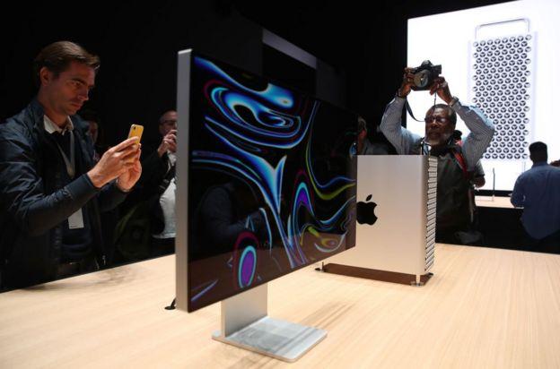 Dos hombres fotografían una Mac Pro