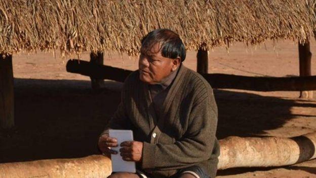 Aritana Yawalapiti, líder do Alto Xingu, sentado em frente a uma construção tradicional