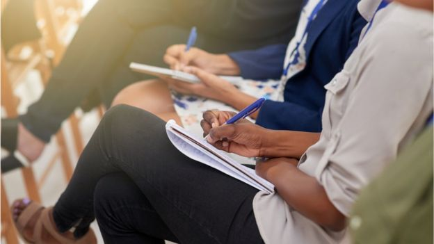 Women taking notes at meeting