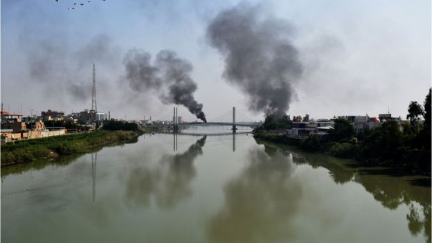 Smoke billows from burning tyres blocking a bridge over the Euphrates River in the centre of the southern Iraqi city of Nasiriyah where demonstrators carried on with anti-government protests on November 12, 2019