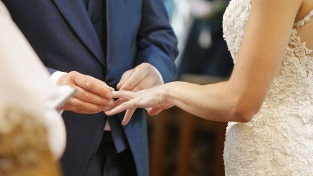 Hombre poniendo anillo a su mujer.
