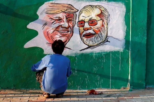 """A man applies finishing touches to paintings of U.S. President Donald Trump and India""""s Prime Minister Narendra Modi on a wall as part of a beautification along a route that Trump and Modi will be taking during Trump""""s upcoming visit, in Ahmedabad, India, February 17, 2020."""