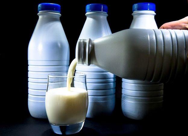 Una persona sirviendo un vaso de leche de una botella. Al fondo, otras tres botellas de leche.