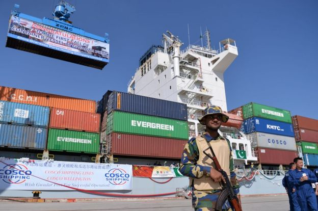 Pakistani Naval personnel stand guard near a ship carrying containers at the Gwadar Port