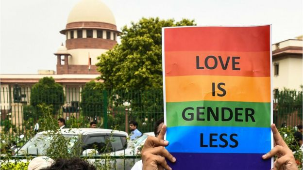 A poster saying Love is Genderless with a backdrop of the Supreme Court