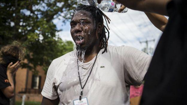 یک معترض برای رهایی از گاز اشک آور از آب استفاده میکند