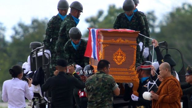 A buddhist monk leads an honour guard carrying the coffin of Samarn Poonan, 38