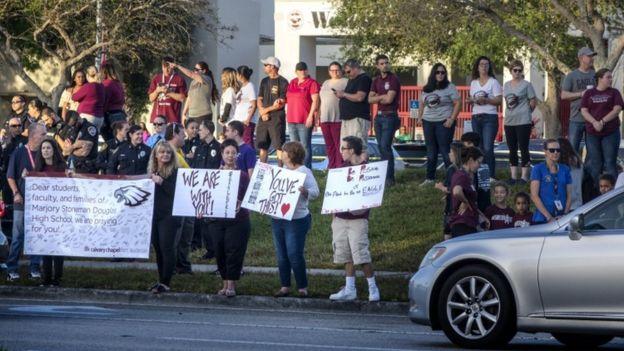 Vecinos y agentes de policía reciben a los alumnos en la puerta de la escuela.