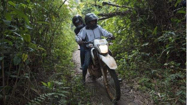Health visitors travelling by motorbike through a remote area of DRC for a follow up meeting with a contact