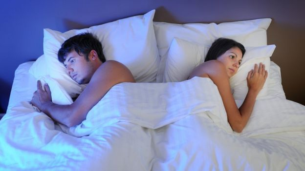 A couple is formed by a man and a woman in bed, to each other.