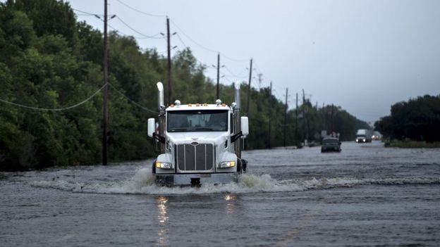 A white truck cab ploughs through deep flood water on a wide open road in Texas near the Arkema plant