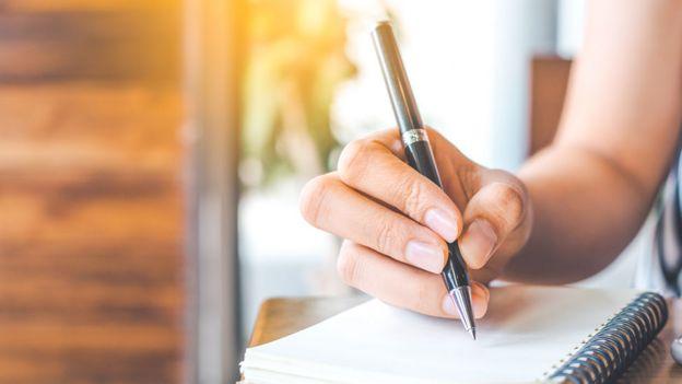 Mano de una joven con una lapicera escribiendo