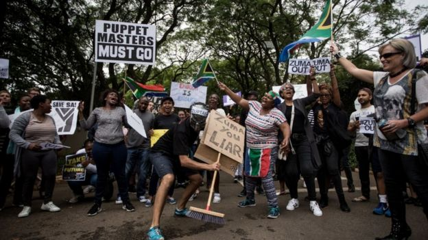 "Demonstrators holding signs such as ""Puppet masters must go"" ""Zuma you liar"""