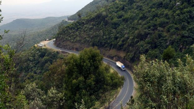 A truck drives on August 21, 2019 on a section of a road leading down the eastern escarpment of the historic Rift Valley, snaking down the cliffside leading from Limuru town
