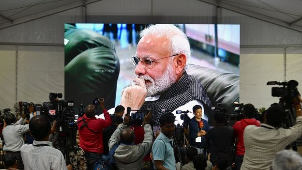 Members of the media cover the development as India's Prime Minister Narendra Modi is seen on a tv screen as he watches the live broadcast of the soft landing of spacecraft Vikram Lander of Chandrayaan-2 on the surface of the Moon at ISRO Telemetry, Tracking and Command Network (ISTRAC) centre in Bangalore early on September 7, 2019.