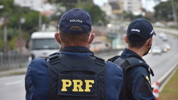 Dois agentes da PRF, identificados por coletes, olham para estrada