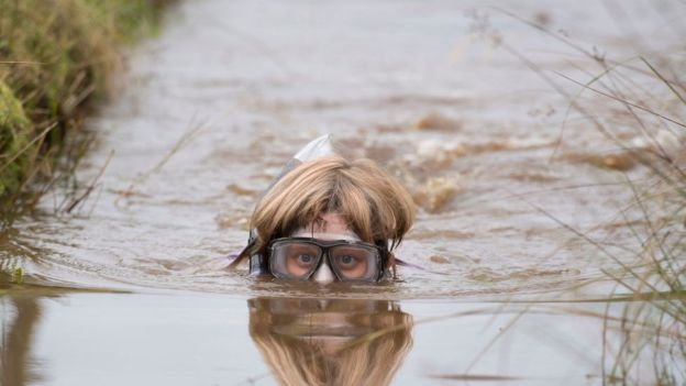 Woman in goggles and snorkel is partly submerged with only her head showing above the water