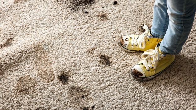 Hombre con zapatillas sucias sobre la alfombra