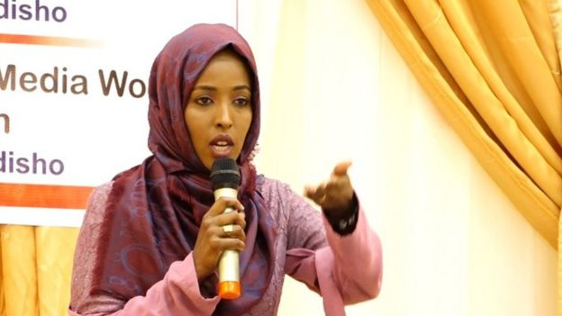 Maryan speaking into a microphone at a conference