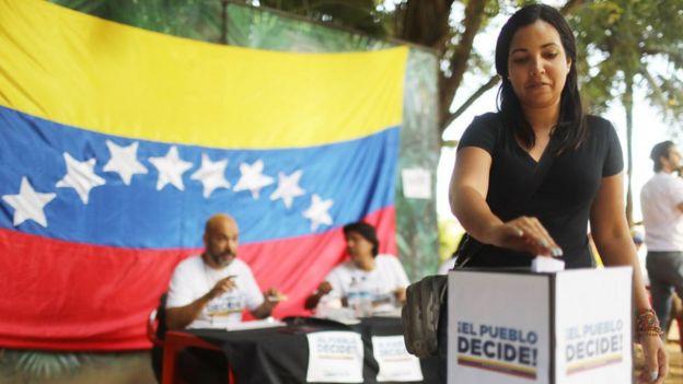 Una mujer deposita su voto durante la consulta popular realizada por la oposición el domingo.