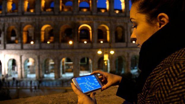 Mulher observa celular à noite