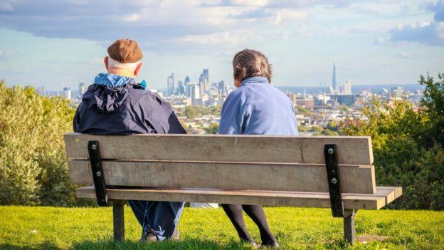 pareja mayor en un parque con vistas a la ciudad