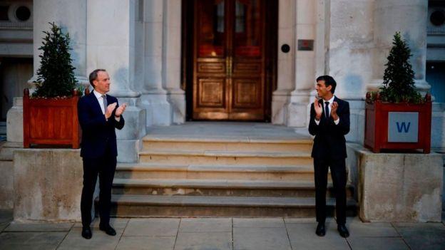 وزير الخزانة البريطاني، ريشي سوناك (إلى اليمين) ووزير الصحة، مات هانكوك، يصفقان للعاملين في مجال الرعاية الصحية