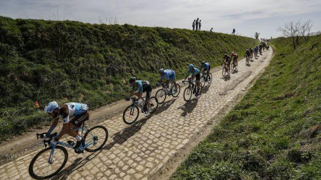 Fila de ciclistas manejando por un camino de adoquines en la carrera París-Roubaix.