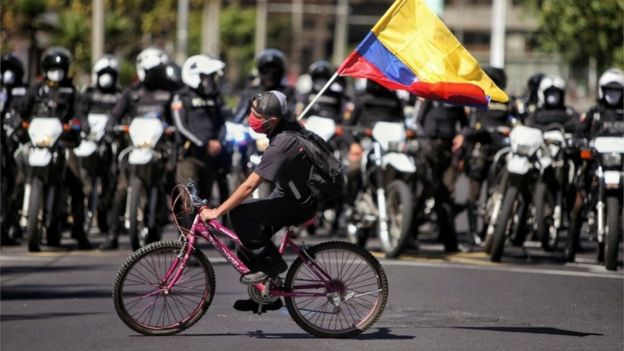 A protester riding a bike waves a flag in front of a row of policemen in Quito