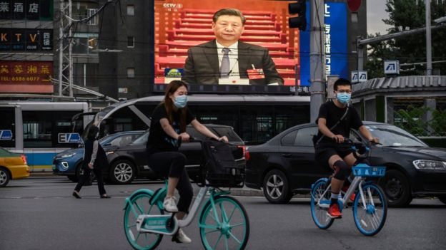 Chinese president Xi Jinping is seen on a large screen in the streets of Beijing