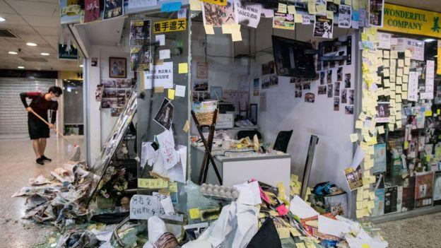 一名黑衣人尝试打扫被示威者破坏的何君尧立法会议员荃湾办事处(22/7/2019)