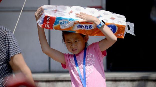 niña cargando un paquete de papel higiénico.