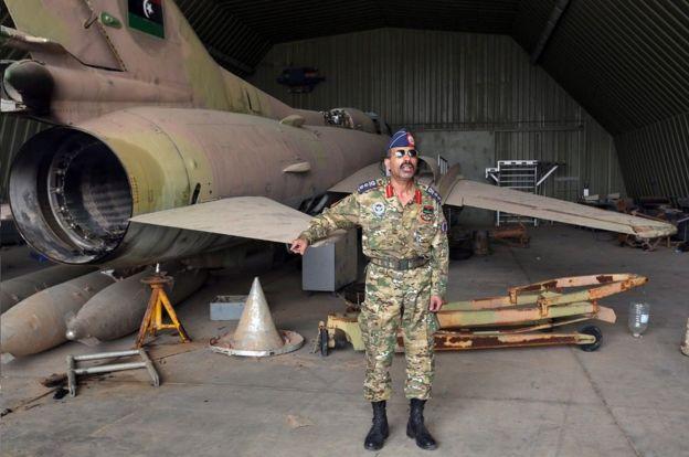 المتحدث باسم قوات الحكومة محمد قنونو بجوار طائرة من طراز ميغ-23 في قاعدة الوطية