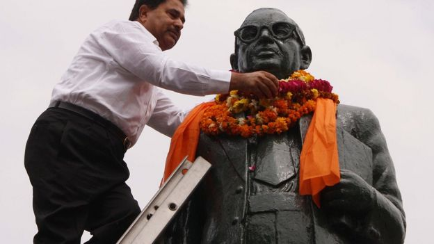 An Indian garlands a statue of BR Ambedkar