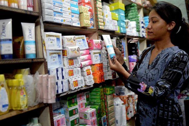 Mujer escoge una crema en una tienda.