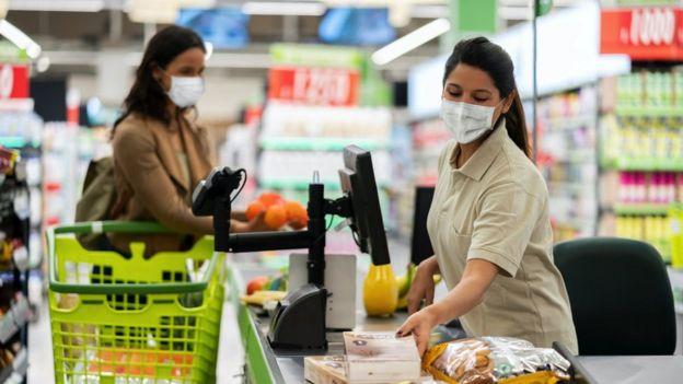 Mulher fazendo compras enquanto outra trabalha como caixa www.aquitemtrabalho.com.br