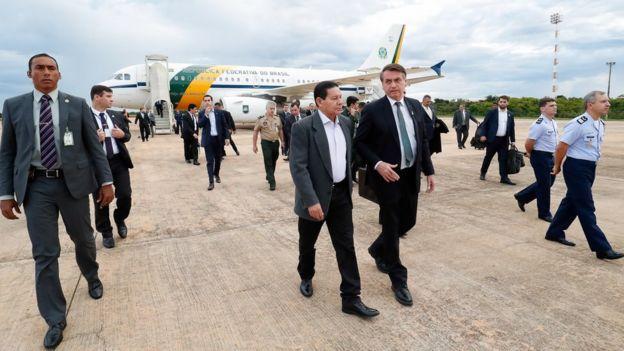 Mourão e Bolsonaro caminham em pista rodeados por seguranças e assessores, com avião no plano de fundo