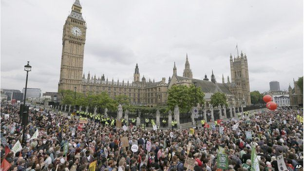 Anti-austerity protesters march past the Palace of Westminster