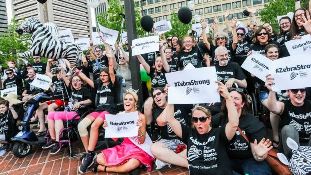 A group of EDS sufferers and supporters hold 'zebra strong' plaques