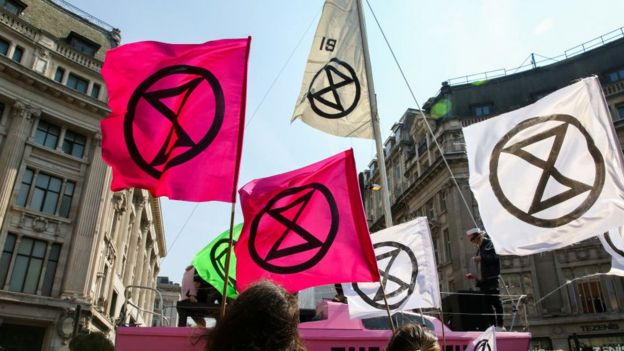 Extinction Rebellion flags with the hourglass logo