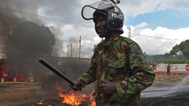 A policeman walks past a burning barricade in Kibera slum in Nairobi on May 23, 2016