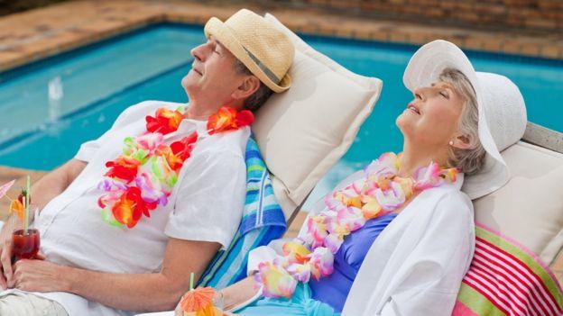 Casal idoso descansa na piscina