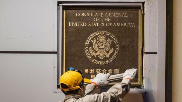 A man attempts to remove the diplomatic plaque form a wall of the US consulate in Chengdu, China. Photo: 26 July 2020