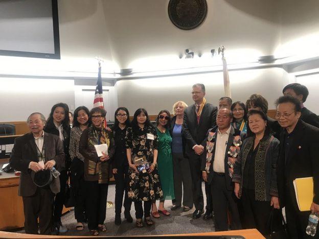 Đại sứ Daniel Kritenbrink vui vẻ nhận quà kỷ niệm là giây đeo có hình ảnh cờ Mỹ và cờ Vàng và chụp ảnh chung với một số khách tham dự buổi gặp gỡ