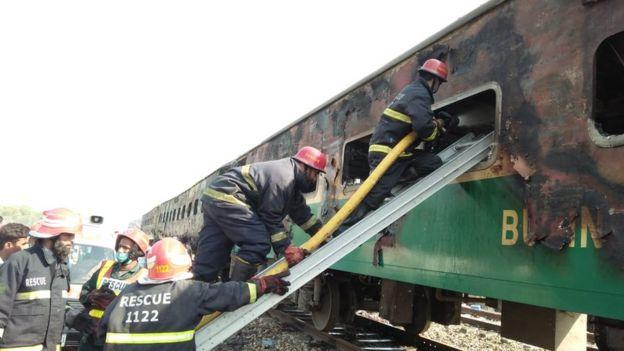 Pakistan firemen board the train that set alight on 31 October