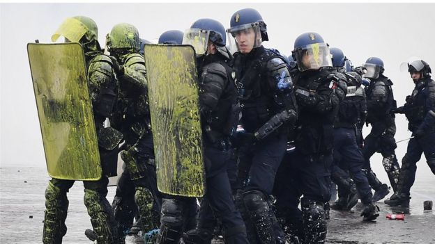 Riot police carry shields covered in yellow paint during protests in Paris on 1 December 2018