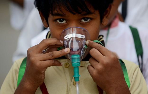 An Indian schoolchild adjusts his facemask before the start of an event to spread awareness of the problem of air pollution in New Delhi on June 4, 2015, on the eve of World Environment Day.
