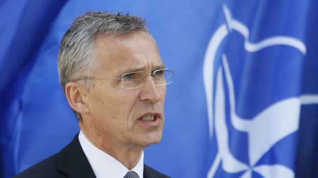 NATO Secretary General Stoltenberg pictured in front of a Nato flag