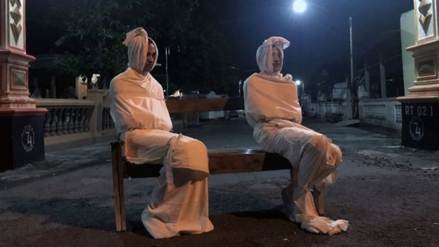 Two volunteers sit dressed as traditional pocong on a bench