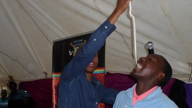 Penuel Mnguni putting a snake in the mouth of a worshipper